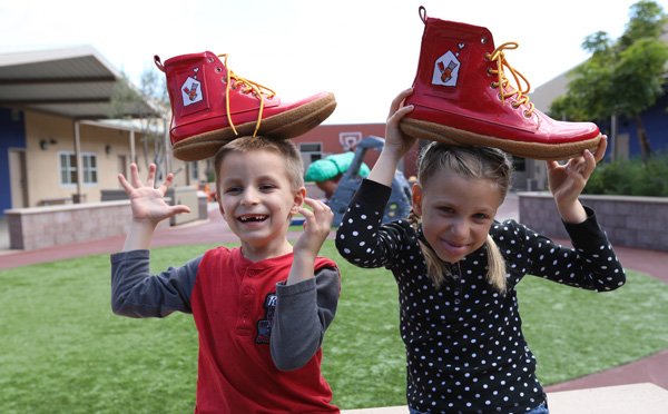 Brother and sister play with Ronald McDonald's size 14 shoes